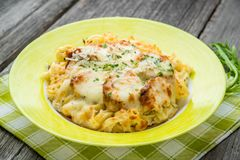 Pasta bake with broccoli and chicken. On a wooden table Stock Photos