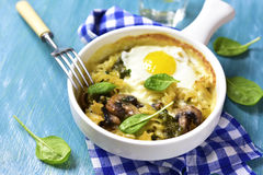 Pasta baked with spinach pesto,egg,mozzarella and mushrooms in a Stock Photo