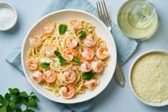 Pasta bavette with fried shrimps, bechamel sauce, mint leaf on blue table, top view, italian cuisine.  stock image
