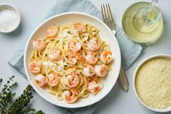 Pasta bavette with fried shrimps, bechamel sauce, thyme on blue table, top view, italian cuisine.  royalty free stock photo