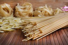 Pasta. Beautiful shot of different types of pasta on wooden background Royalty Free Stock Images