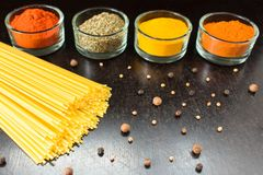 Pasta on black background and spices stock photography