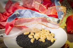Pasta and black beluga lentils and a pile of gift ribbons Stock Photos