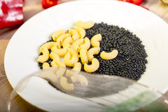 Pasta and black beluga lentils on a white plate Royalty Free Stock Photos