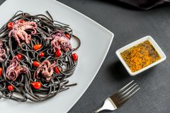 Pasta with black cuttlefish ink and small octopuses. Close up Royalty Free Stock Photography