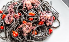 Pasta with black cuttlefish ink and small octopuses Royalty Free Stock Photos