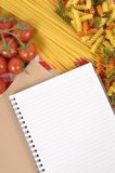Italian pasta with blank recipe book, cookbook, and chopping board, copy space Royalty Free Stock Photos