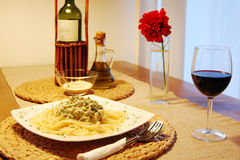 Pasta with broccoli. On a white plate. Decorationn of red flower, bottle of wine and olive oil Royalty Free Stock Image