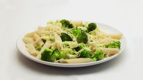 Pasta with Broccoli and Grated Cheese on a White Plate stock images