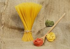 Pasta Beside Brown Wooden Laddle on Brown Knitted Textile Stock Images