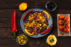Pasta and burning peppers on a gray plate with tomatoes, sweet pepper, lemon, olives and olives on a wooden dark Stock Images