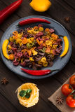 Pasta and burning peppers on a gray plate with tomatoes, sweet pepper, lemon, olives and olives on a wooden dark Stock Photography