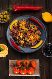 Pasta and burning peppers on a gray plate with tomatoes, sweet pepper, lemon, olives and olives on a wooden dark Stock Photos