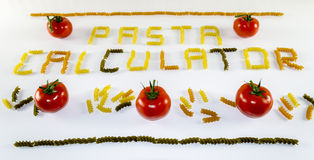 Pasta Calculator. Pasta spelled using dried twists of Fusili and some red tomatos Royalty Free Stock Photos