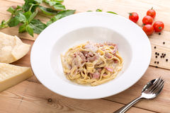 Pasta carbonara with bacon. On wooden background with ingredients Royalty Free Stock Photos