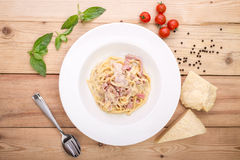 Pasta carbonara with bacon. On wooden background with ingredients Stock Photo