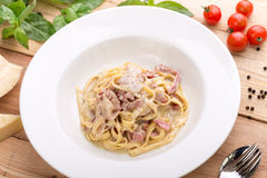 Pasta carbonara with bacon. On wooden background with ingredients Stock Photos