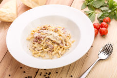 Pasta carbonara with bacon. On wooden background with ingredients Stock Image