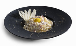 Pasta carbonara decorated with slices of parmesan and yolk isolated. Carbonara pasta with pieces of roasted bacon garnished with thin slises of parmesan cheese stock images