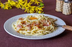 Pasta Carbonara. Flowers in the background. Italian food stock photos