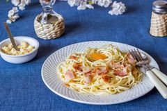 Pasta Carbonara. Flowers in the background. Italian food royalty free stock image