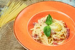Pasta Carbonara. Gray textured background with beige fabric. Beautiful serving of dishes. Restaurant menu. Pasta carbonara with egg and basil on an orange plate royalty free stock images