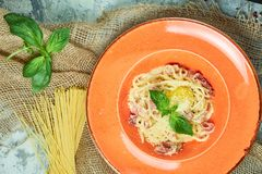 Pasta Carbonara. Gray textured background with beige fabric. Beautiful serving of dishes. Restaurant menu. Pasta carbonara with egg and basil on an orange plate stock images