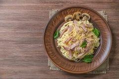 Pasta Carbonara med bacon och champinjoner i keramisk disk på tabellen som göras av ekplankor medf8ort övre sikt Kopieringsbrunns arkivfoton