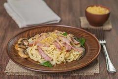 Pasta Carbonara med bacon och champinjoner i keramisk disk på tabellen som göras av ekplankor medf8ort övre sikt Kopieringsbrunns arkivfoto