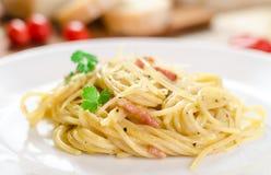 Pasta Carbonara med bacon på en vit platta Royaltyfri Foto