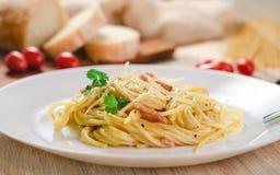 Pasta Carbonara med bacon på en vit platta Royaltyfria Bilder