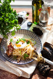 Pasta Carbonara on plate with bacon and egg plows on dark wood b. Ackground Stock Images