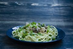 Pasta carbonara with pork, fresh herbs, sprinkled with sesame on top of a blue plate. Dark wooden background. Side view stock photos