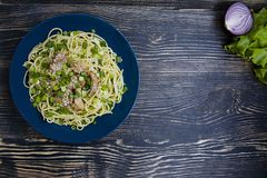 Pasta carbonara with pork, fresh herbs, sprinkled with sesame on top of a blue plate. Dark wooden background. View from above stock images