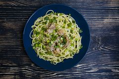 Pasta carbonara with pork, fresh herbs, sprinkled with sesame on top of a blue plate. Dark wooden background. View from above stock photo