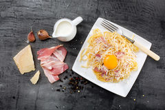 Pasta Carbonara. Spaghetti with bacon and parmesan cheese.  on white plate with parmesan on dark background Stock Images