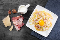 Pasta Carbonara. Spaghetti with bacon and parmesan cheese.  on white plate with parmesan on dark background Stock Image