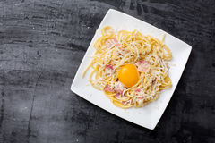 Pasta Carbonara. Spaghetti with bacon and parmesan cheese.  on white plate with parmesan on dark background Royalty Free Stock Image