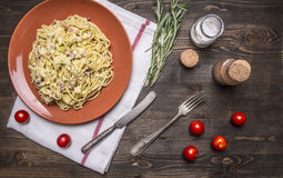 Pasta carbonara with zucchini, in a brown plate with vintage knife and fork, with herbs and spices on rustic wooden background top. Pasta carbonara with zucchini Royalty Free Stock Photos