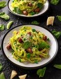 Pasta casalinga con i piselli, il pesto degli spinaci e le salsiccie Isolato su fondo bianco Alimento sano immagini stock
