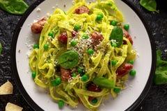 Pasta casalinga con i piselli, il pesto degli spinaci e le salsiccie Isolato su fondo bianco Alimento sano Fondo immagini stock