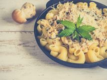 Pasta cavatappi with cepes in a iron pan on the wood table. stock photo