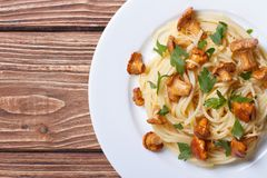 Pasta with chanterelles closeup on wooden top view Stock Image