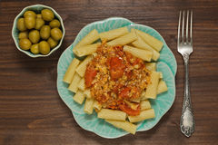 Pasta with cheese and tomato sauce and pickled green olives. Pasta dish with tomato and parmesan cheese sauce with garlic and pepper and pickled green olives royalty free stock photo
