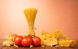 Pasta, cheese and tomatoes on brown background. Royalty Free Stock Images