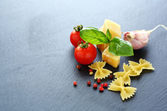 Pasta, cheese and tomatoes on slate background Royalty Free Stock Photography