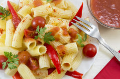 Pasta with cherry tomatoes and red pepper served with a tomato s Royalty Free Stock Photos