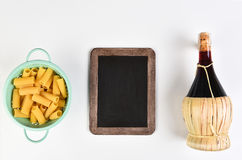 Pasta Chianti Chalkboard. Top view of a blank chalkboard with a colander filled with rigatoni pasta and a bottle of Chianti wine. Horizontal format on white stock images