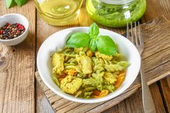 Pasta with chicken pieces and pesto sauce on an old wooden table. Pasta with chicken pieces and pesto sauce on an old wooden table Stock Photo