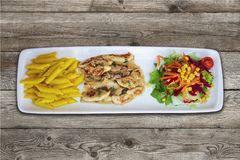 Pasta, chicken and salad. Top view on wooden floor stock images